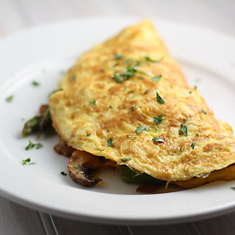 White plate with folded omelete made with asparagus and mushrooms.